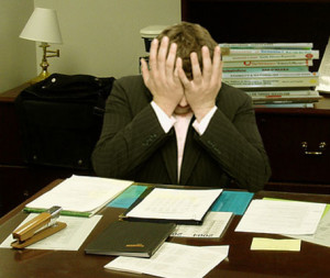 Frustrated_man_at_a_desk_cropped-300x253